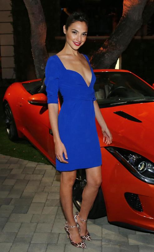 Gal Gadot vestida de azul, con un coche rojo... solo le falta el amarillo y el látigo